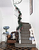 Staircase decorated for Christmas, white candles on steps, small dog on the side on a comfortable leather armchair