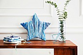 DIY decorative stars wrapped in wool in shades of blue and arranged decoratively with a glass vase and gifts