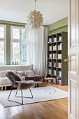 Sheepskin blanket on classic chair, stool and sofa below window next to bookcase against green wall
