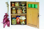 Jars of preserved vegetables in wall-mounted cupboard with open door next to string of onions