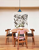 Holzstühle mit lederbezogenem Sitzpolster um Tisch mit Retroflair vor Wand mit modernem Bild