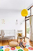 Kind auf Teppich mit buntem Knopf-Muster und Freischwinger-Sessel neben weißem Gitterbett