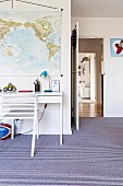 Youth room with striped carpeting, white desk and hung map