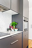 View of the anthracite-colored kitchenette with marble kitchen worktop and splash guard