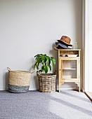 Display cabinets with stacked hats, house plants in wicker planters and wicker bags on carpeted floors