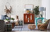 Wohnraum mit maritimem Flair; Korbsessel und Fusshocker, folkloristische Beistelltische und beigefarbene Mustertapete
