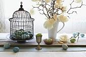 Österliches Stillleben mit bunten Eiern, Deko-Vogelkäfig und Magnolienstrauss