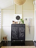 Black chest of drawers labeled with chalk against a wood-paneled wall
