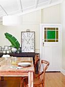 Holz-Esstisch und Holzstühle mit Korbgeflecht vor gerahmter Vintage-Uhr auf Sideboard im Dachgeschoss