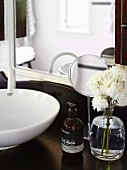 White flowers and soap dispenser in front of cosmetic mirror on vanity with traditional flair