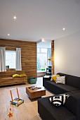 Corner sofa, wood-clad wall and custom bench in lounge area