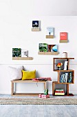Decorative wall shelves with books on wooden bench and bookcase