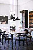 Esszimmer im Ethno-Look mit dunklen Möbeln und Designklassikern