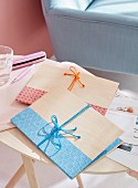 Homemade folders made from wood veneer decorated with strips of paper and bows