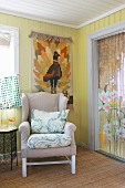 Wing-back chair below tapestry on board wall and next to Oriental bead curtain