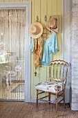 Gilt chair below coat rack on yellow wall