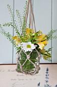 Glass vase of flowers in macrame hanger