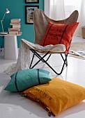 In verschiedenen Farben gefärbte Kissenhüllen auf Butterfly Sessel und auf Boden