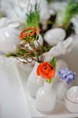 weiße Osterdekoration mit roten Blüten auf weißem Tisch