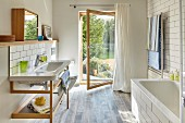 Washstand with wooden base unit and open glass door with garden view in bright modern bathroom