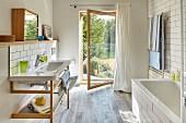 Waschtisch mit Holz Untergestell und offene Glastür mit Gartenblick in hellem, modernem Bad