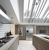 Designer kitchen with wooden board fronts under glass roof