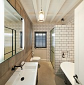 Shower cabinet and free-standing bathtub in narrow, purist bathroom