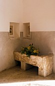 Old stone sink in corner below two small niches in two-tone walls