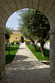 View through Mediterranean archway along paved path leading through garden