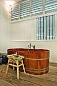 Free-standing wooden bathtub with Oriental stool as side table
