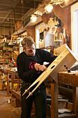 Junger Handwerker arbeitet an Kuckucksuhr an der Schnitzbank
