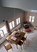 View down into renovated dining room in old wooden house with open sloping roof