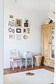 Pastellfarbene Hocker unter Bilderwand neben altem Schrank