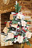 Christmas tree decorated with DIY Advent calender made from envelopes tied with ribbons