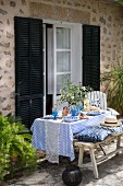 Set, summer dining table on terrace outside Mediterranean house