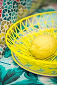Lemon in yellow basket on colourful plate