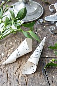 Sheet-music cones and sprigs of mistletoe on rustic wooden surface