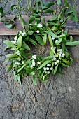 Wreath of mistletoe and berries on a rustic wooden table