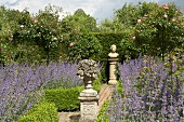 Sculptures on stone plinths on garden path amongst beds of lavender, box hedges and standard roses