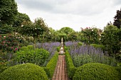 Brick-paved path leading through beds of clipped hedges, standard roses and box balls to stone sculptures on plinths