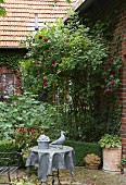Rose bush in summer flowerbed against brick façade, metal garden furniture and grey sculpture