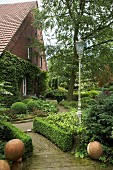 Paved garden path leading between herbaceous borders, box hedges and stone spheres to country house with brick façade