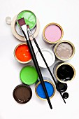 Various pots of paint, paintbrushes and masking tape seen from above