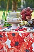 Tisch im Garten gedeckt mit roter Blumentischdecke, Kuchen und Korb mit Äpfeln