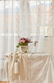 Flower arrangement and duck-shaped carafe on small table with off-white lace tablecloth in front of window with lace curtains