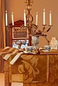 Herbstliche Tischdekoration mit goldfarbenen Tischläufern und Kronleuchter mit brennenden Kerzen