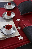 Festive table decoration in red and grey with place mats, tablecloth, napkins and cushion