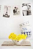 Bowl of primroses below vintage-style postcards on wall