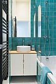 Bathtub and turquoise tiles in narrow bathroom