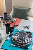 Table set with colourful mats, spotted plates and black drinking glasses